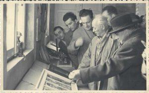 """marzo 1953: inaugurazione della nuova sede della Scuola Comunale d'Arte e Mestieri di Cotignola. Il Direttore prof. Luigi Varoli illustra al Ministro Aldisio e all'On. Zaccagnini l'opera in ceramica """"le quattro stagioni"""" di Ghinassi, uno dei pezzi maggiormente ammirati della Rassegna Artistica degli allievi."""
