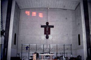 Davanti al ponteggio per l'installazione del pannello della Redenzione si nota il Crocefisso dipinto da Sante Ghinassi a tempera su supporto ligneo, ora collocato nella Chiesa di Sassoleone (Imola).